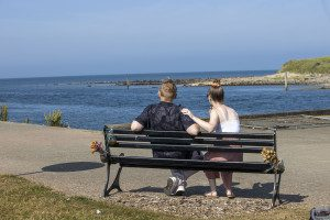 Brian and Claire are sitting on a bench with their backs to the camera, looking out at the sea, it is a sunny day