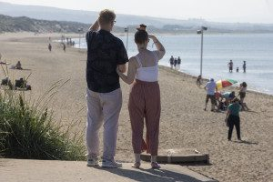 Brian and Claire are standing arm in arm with their backs to the camera, looking out at a beach