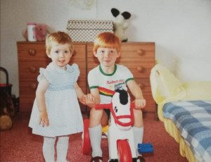 Claire and Brian are small children holding hands in a bedroom, Brian is sitting on a rocking horse and they are both smiling